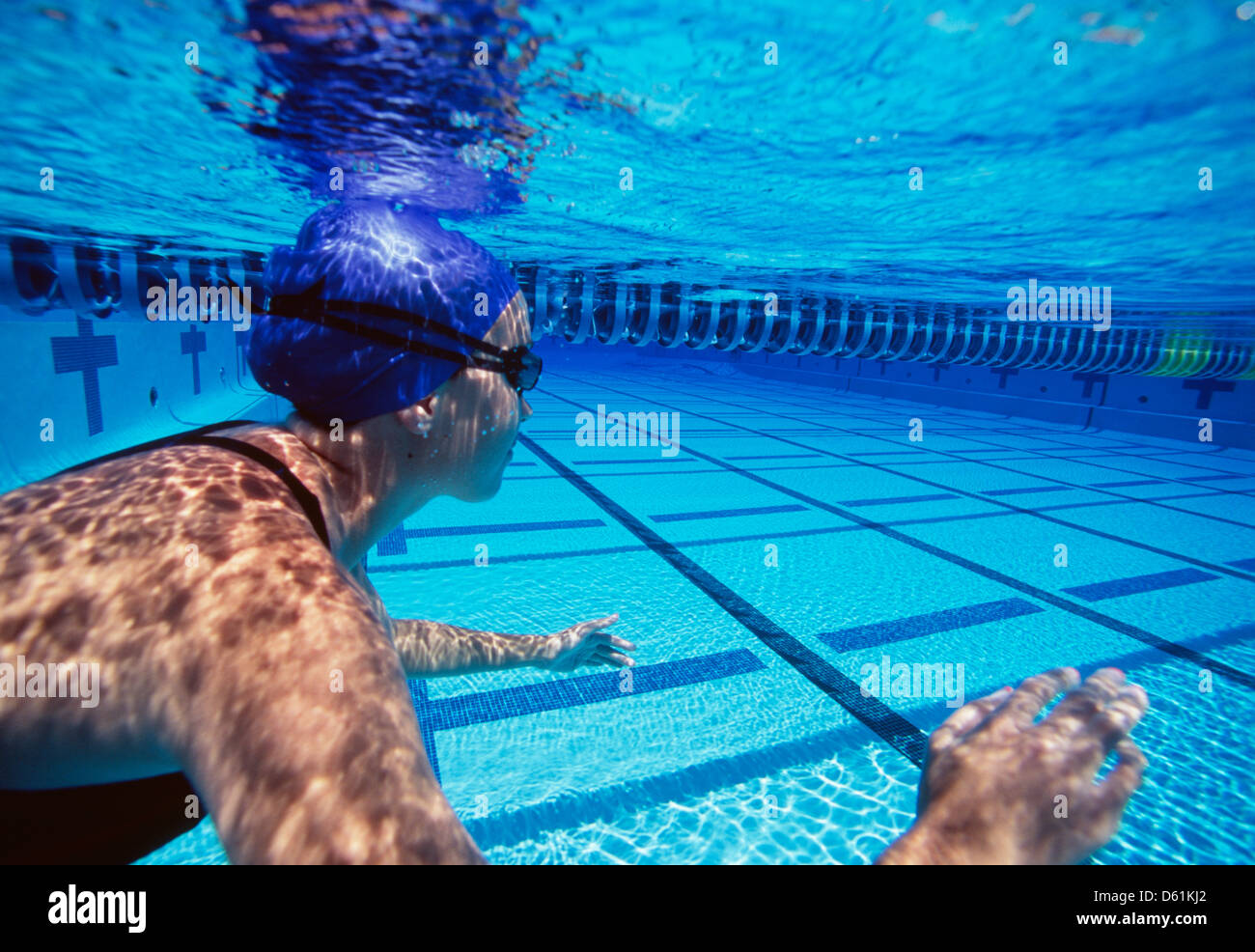 Caucasian female swimmers swimming in pool - Stock Image