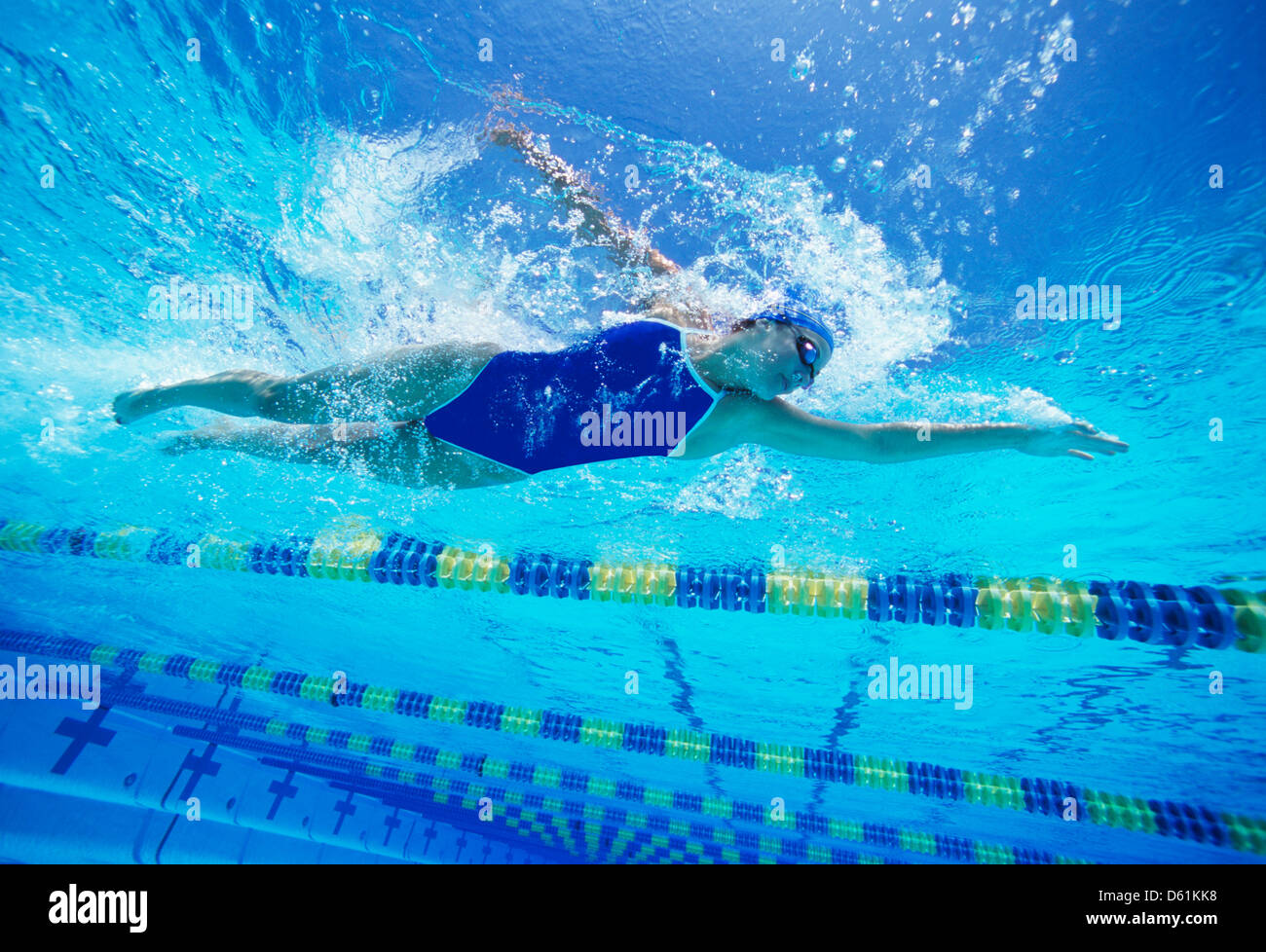 Female swimmer wearing United States swimsuit while swimming in pool - Stock Image
