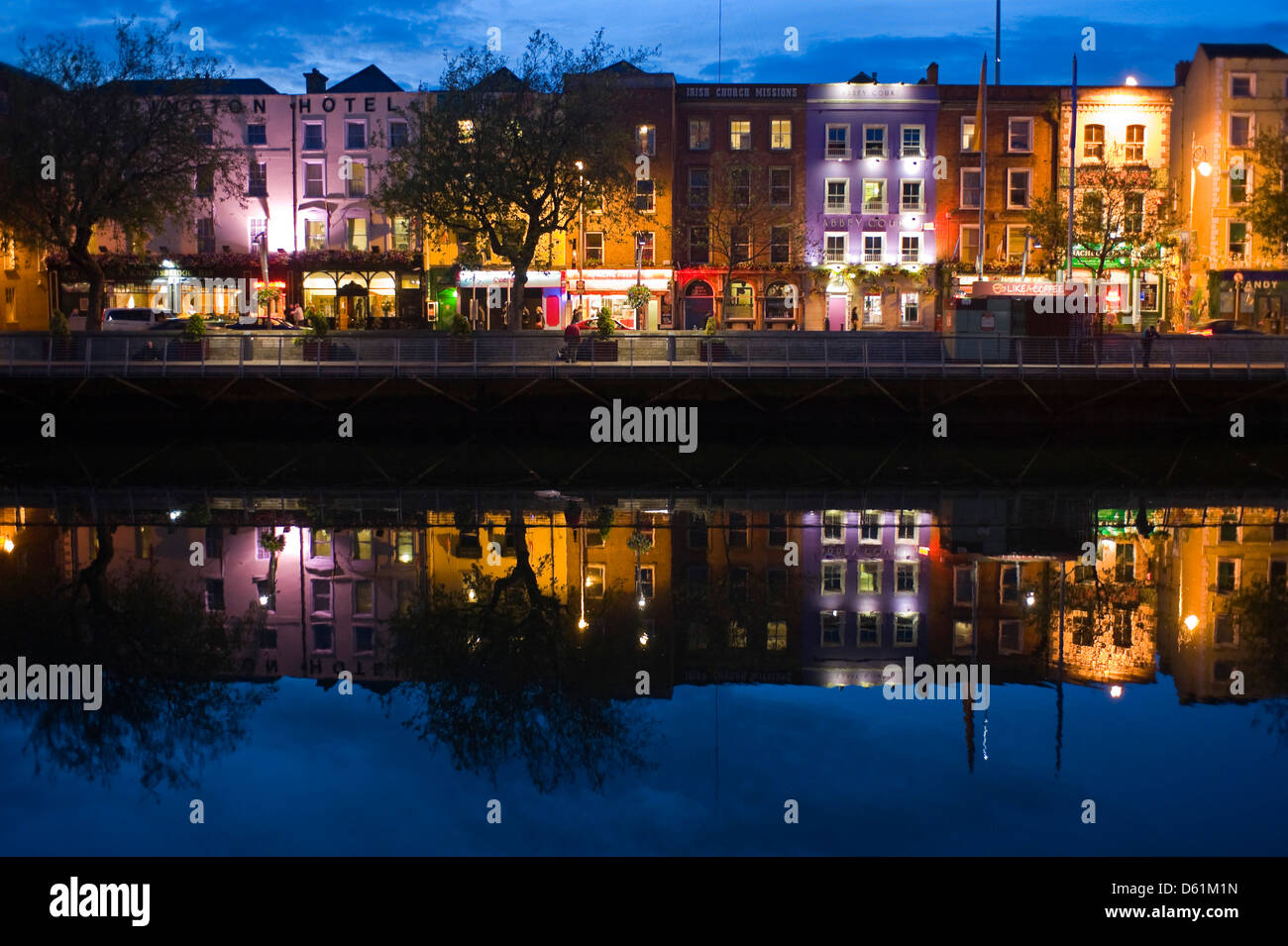 Horizontal view of the colourful buildings along Batchelor's Walk reflected in the River Liffey in Dublin at night. Stock Photo