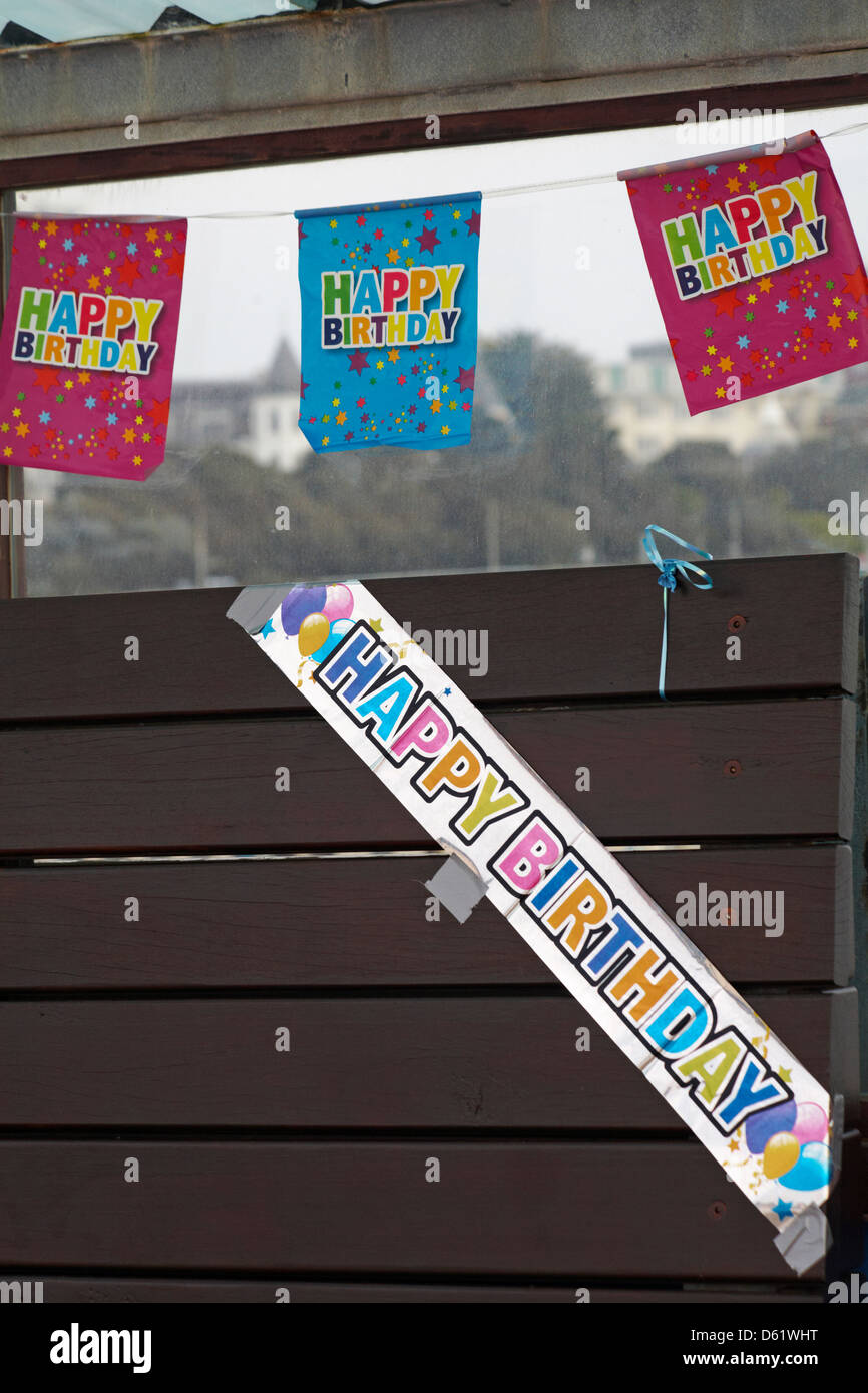 Happy Birthday banners draped around seat on Bournemouth pier in March - Stock Image