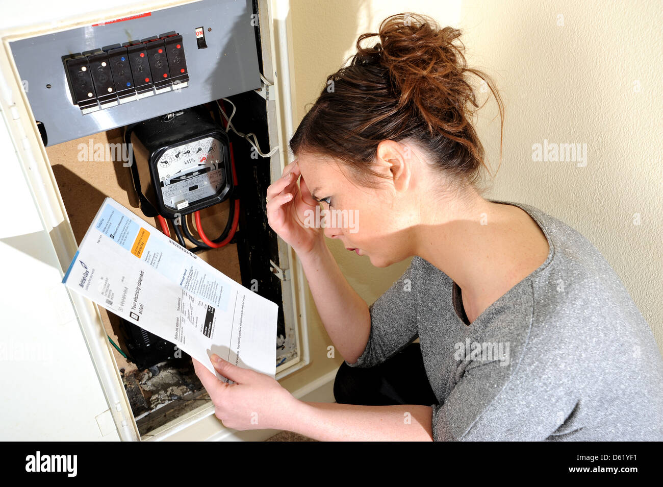 Young woman 20s attempting to read and understand her electricity meter reading and energy bill - Stock Image