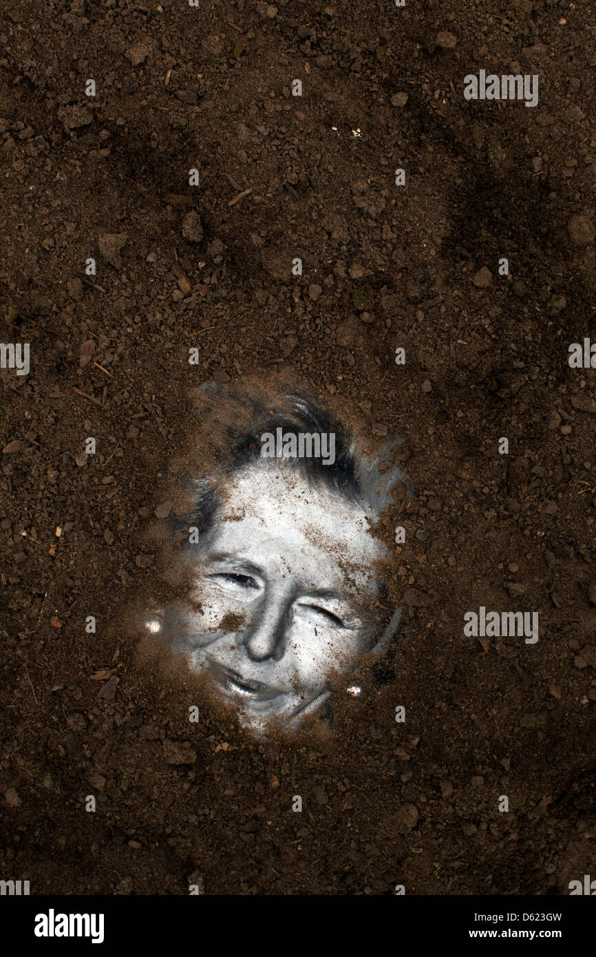 Tramp the dirt down. A picture of former British Prime Minister Margaret Thatcher is buried in soil - Stock Image