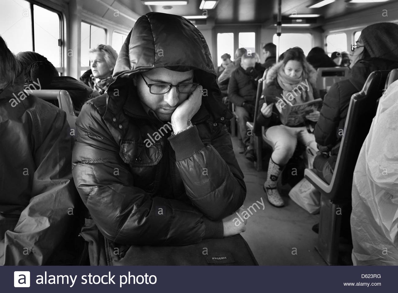 Passengers on a Vaporetto, Venice, Italy. A man, heavily wrapped against the cold, snoozes in his seat on his way - Stock Image