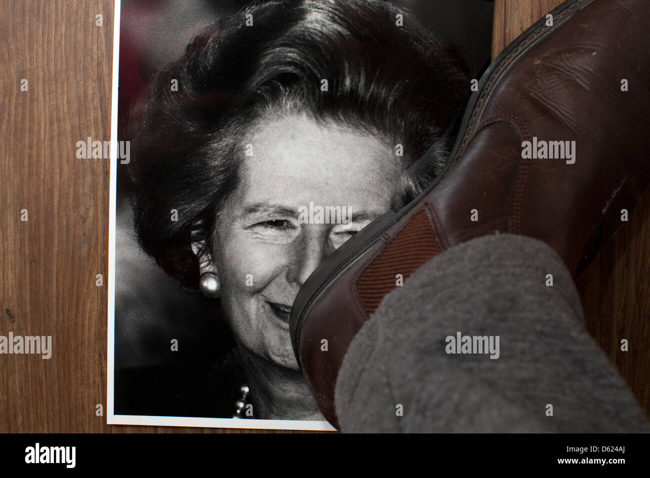 Tramp the dirt down. A picture of former British Prime Minister Margaret Thatcher is  stamped on - Stock Image