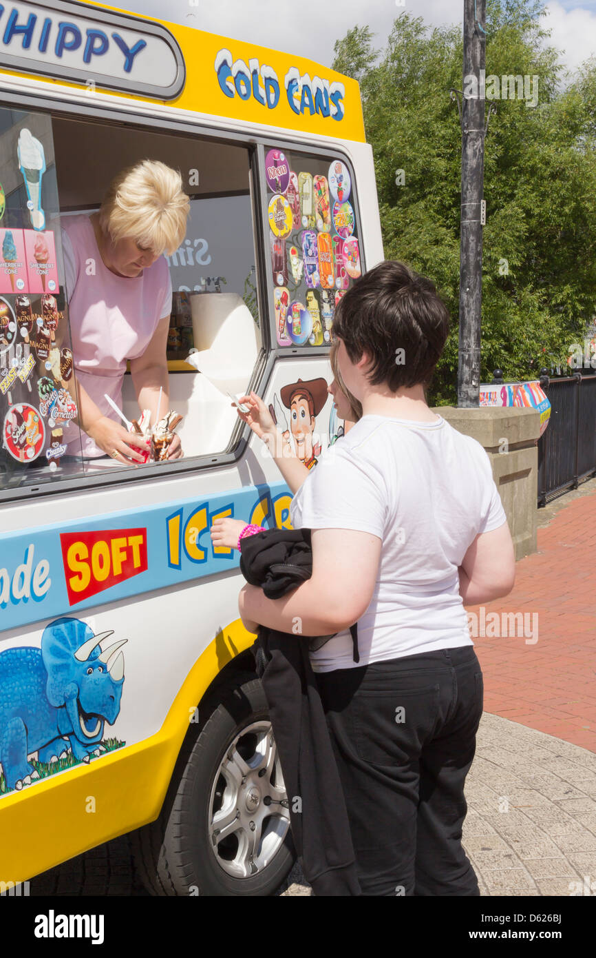 A teenage boy and girl buy ice cream from an ice cream van.  The ice cream seller is an adult woman with blond hair. - Stock Image