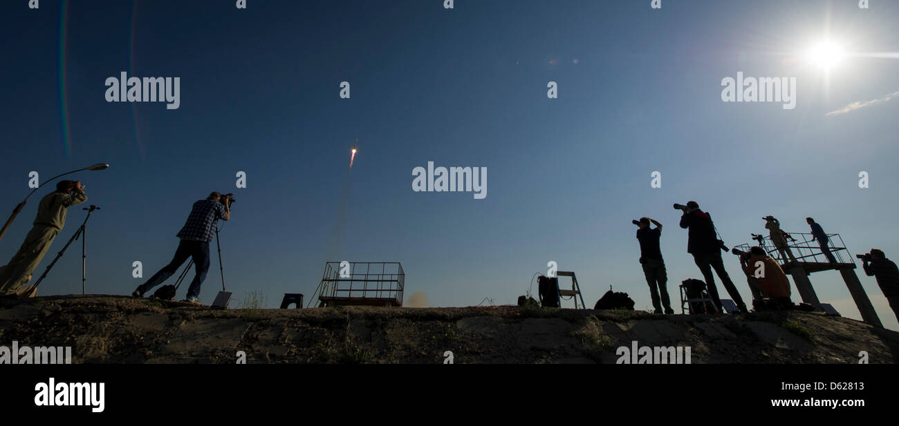 Members of the media photograph the Soyuz TMA-04M rocket launch from the Baikonur Cosmodrome in Kazakhstan on Tuesday, - Stock Image