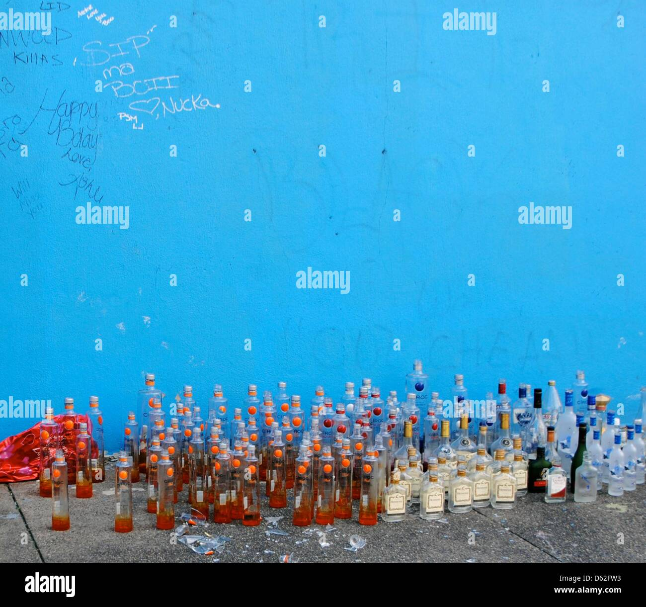 Gang members commemorate a deceased friend with bottles of schnapps instead of flowers in Camden, USA, 12 March - Stock Image