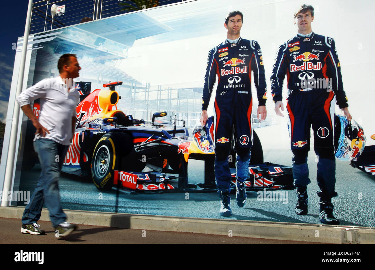 A man walks in front of a billboard on the floating motor home of Red Bull with the images of German Formula One driver Sebastian Vettel (L) and Mark Webber (R) prior to the Formula One Grand Prix of Monaco in Monte Carlo, Monaco, 22 May 2012. The Grand Prix will take place on 27 May. Photo: Jens Buettner dpa Stock Photo