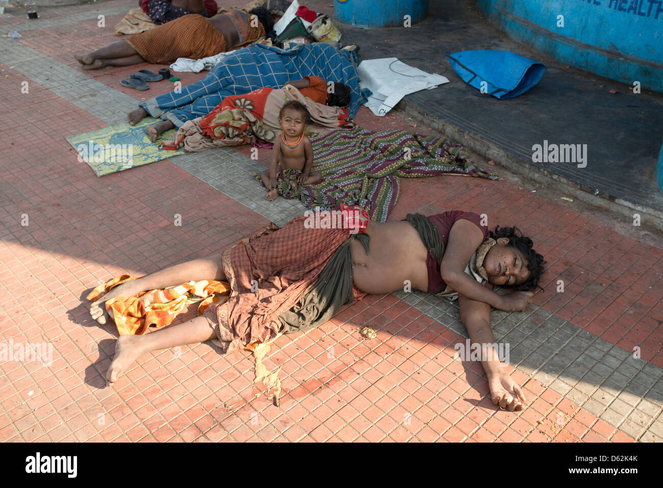 A child weeps while his destitute mother sleeps in Chennai, Tamil Nadu, India - Stock Image