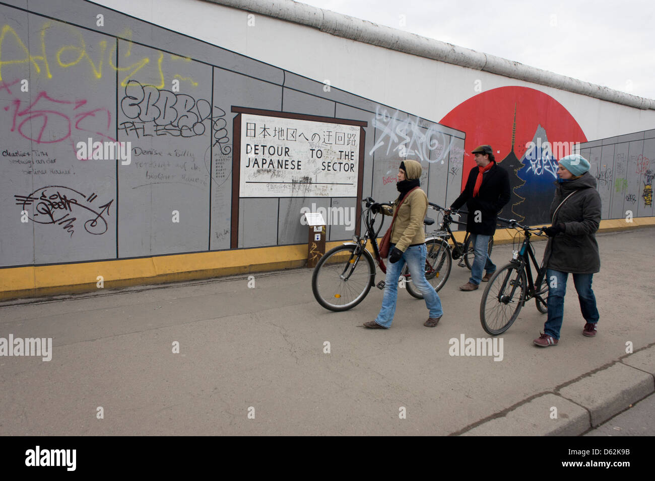 Visitors Enjoy The Art On The Old Berlin Wall At The East Side Gallery, The  Former Border Between Communist East And West Berlin During The Cold War.