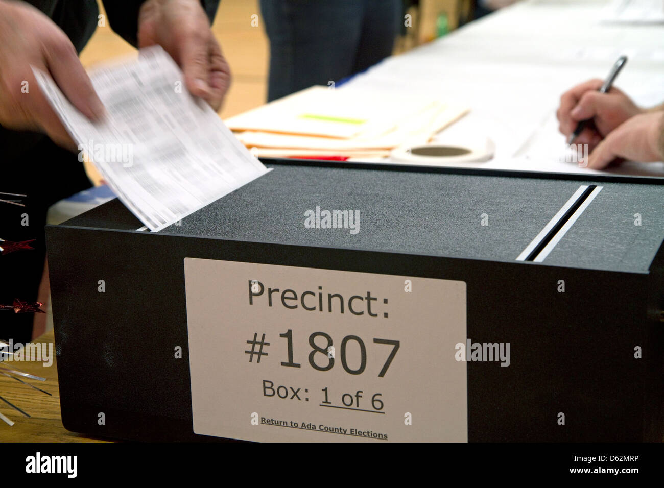 Voted ballot being put into a ballot box in Boise, Idaho, USA. - Stock Image