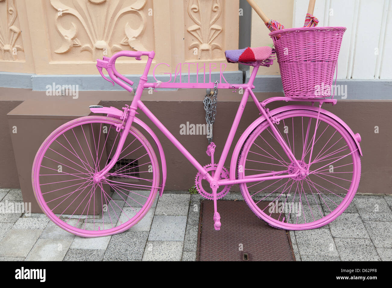 Pink painted bike as an advertisement in Napier, New Zealand - Stock Image