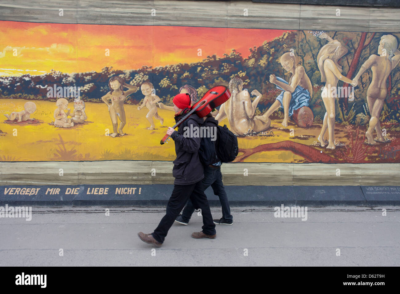 Visitors enjoy the art on the old Berlin Wall at the East