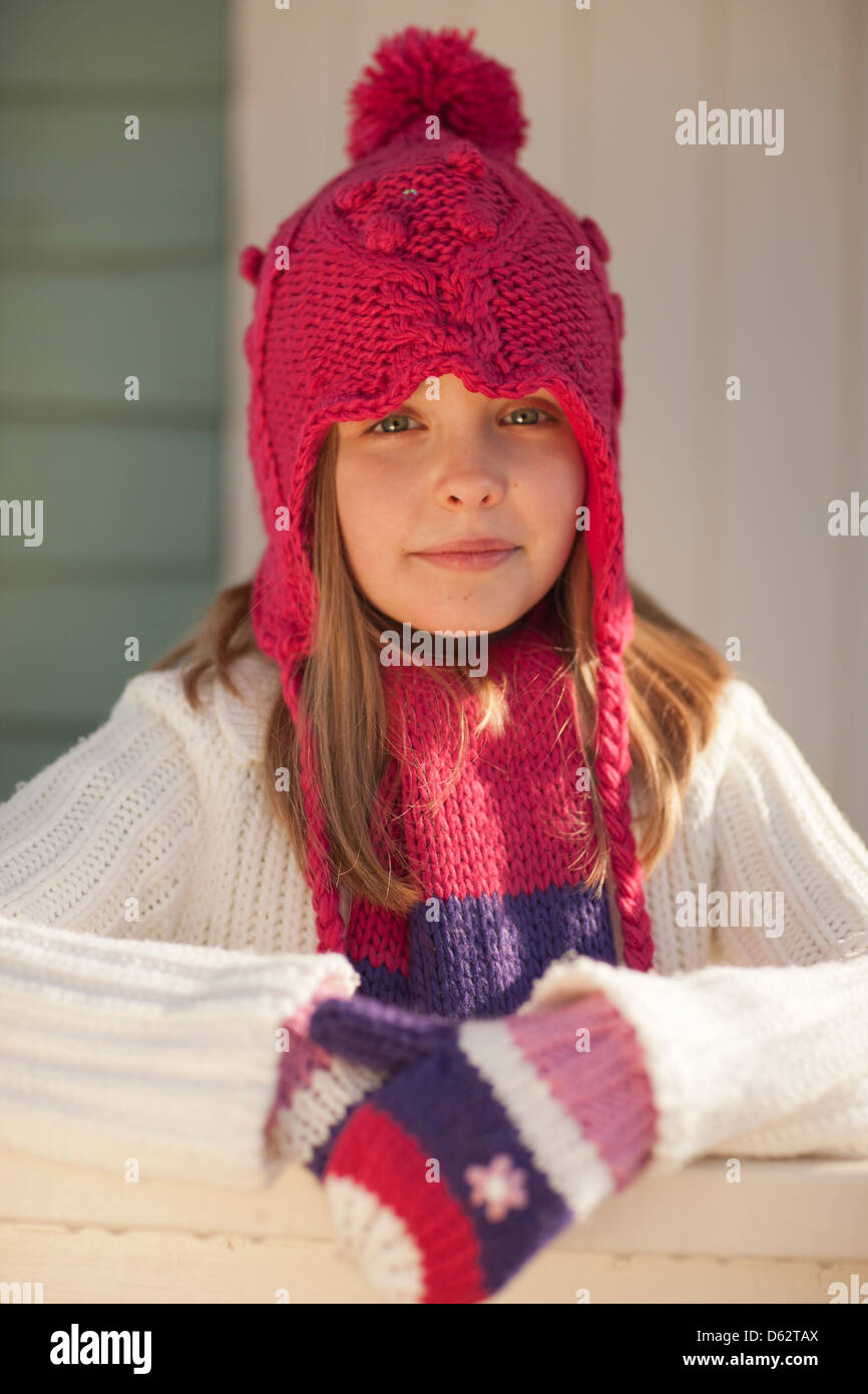 Portrait of a cute young girl in pink hat and Winter clothing on beach at Hunstanton, Norfolk, UK - Stock Image