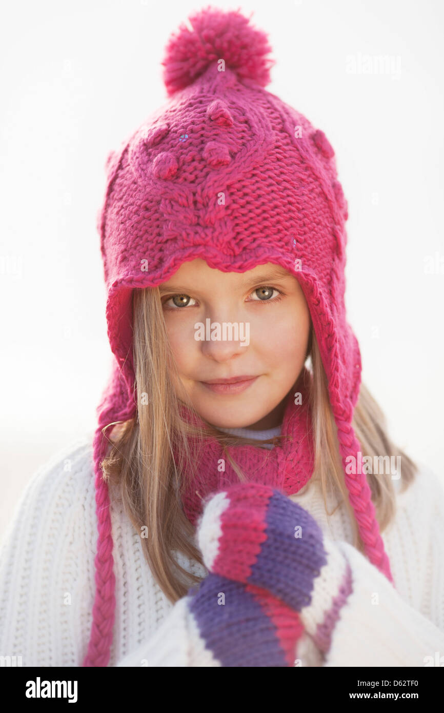 Portrait of a cute young girl in pink hat and Winter clothing on beach at Hunstanton, Norfolk, UK Stock Photo