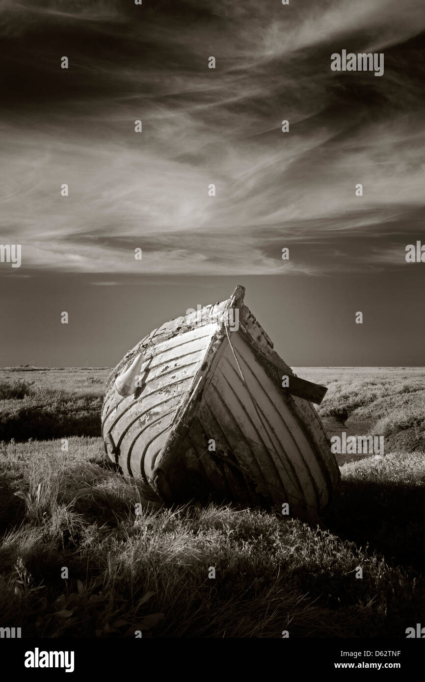 Lonely old wooden fishing boat on the saltmarshes at Burnham Deepdale in Norfolk, UK Stock Photo