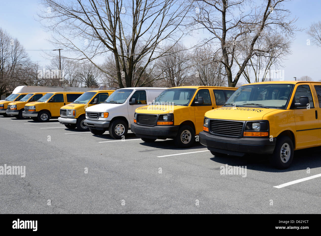 row of many yellow and white vans used to transport students to and from school - Stock Image