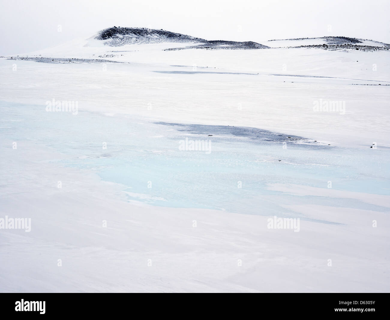 melt water and snow-covered lava fields and mountain hills on Northern Iceland - Stock Image