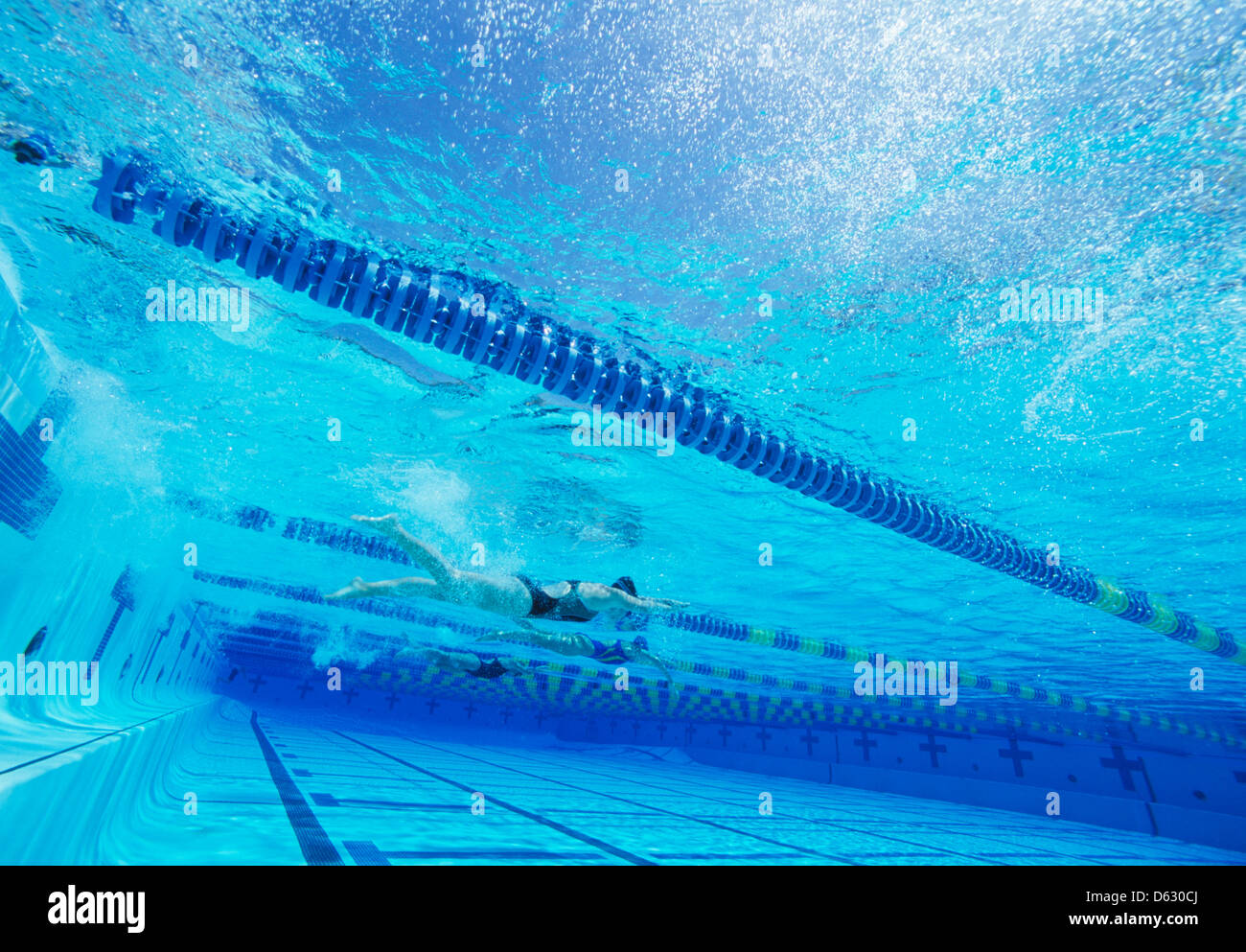 Swimmers racing together in swimming pool - Stock Image