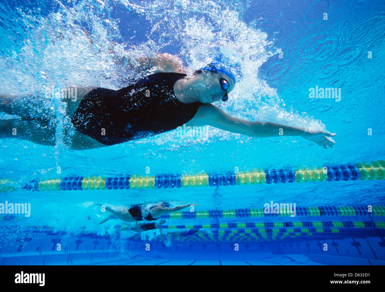 Professional female swimmers swimming in pool - Stock Image