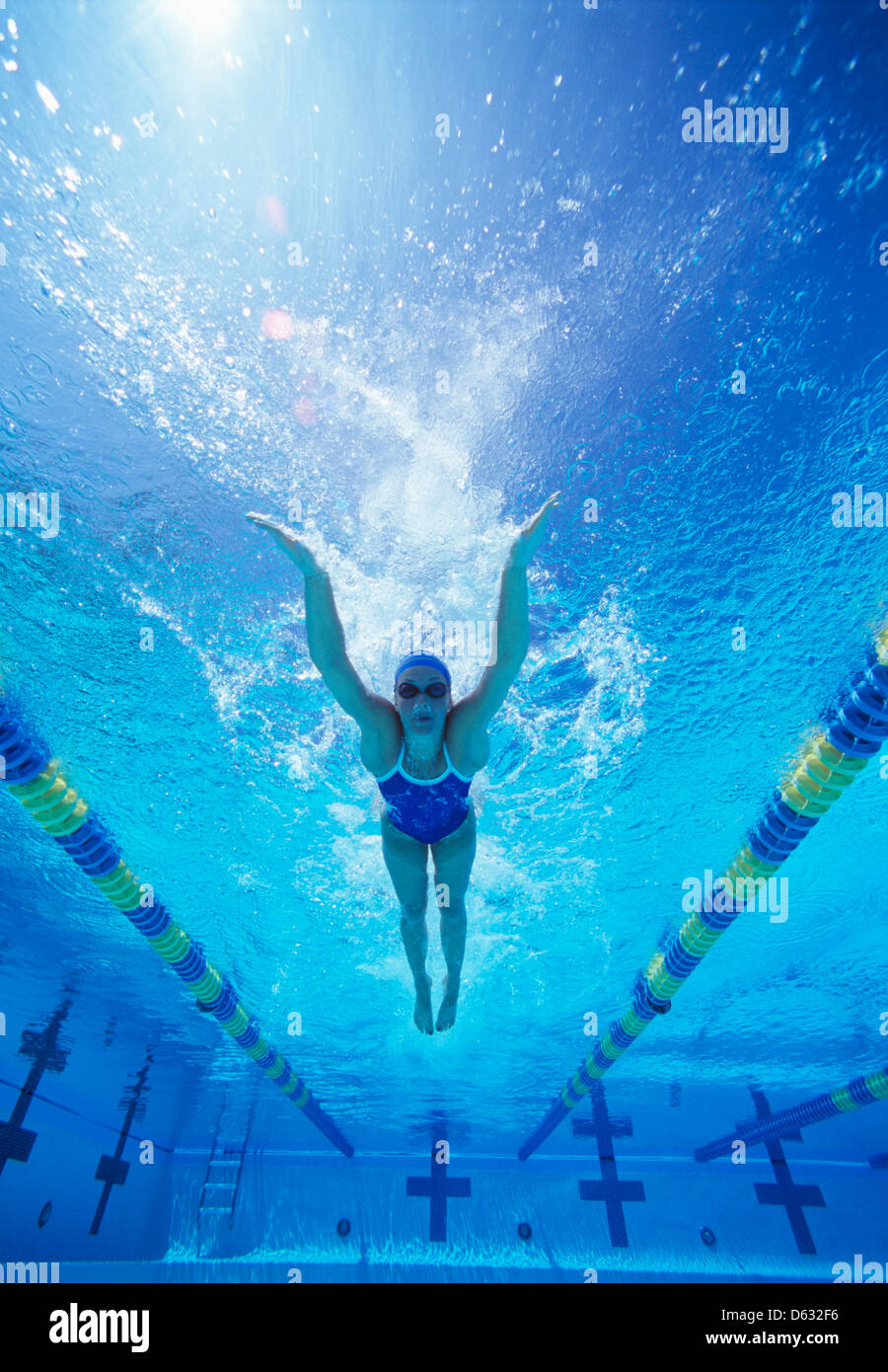 Full length of female swimmer in United States swimsuit swimming in pool - Stock Image