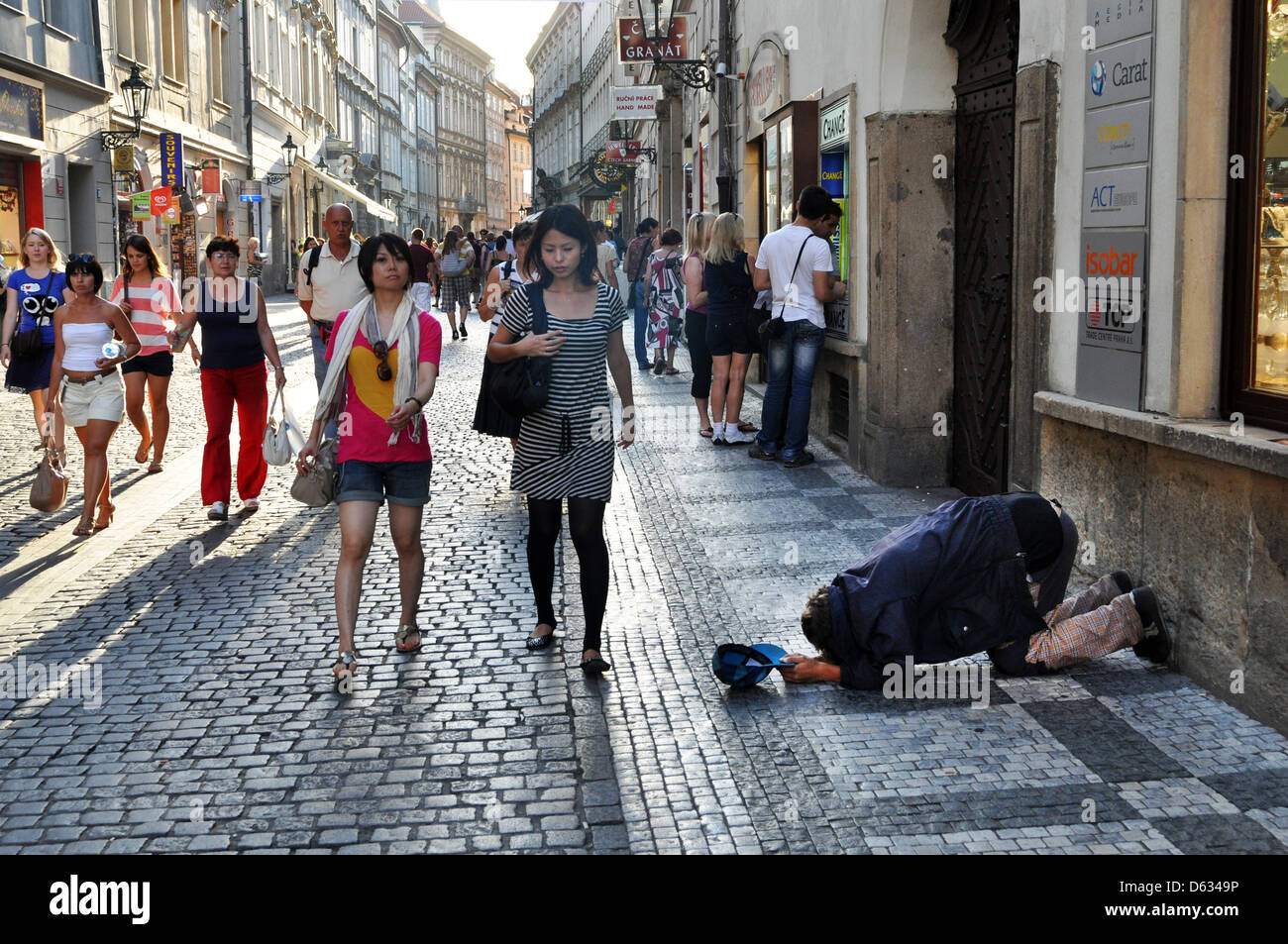 Beggar bows down on his knees on a Prague street, Czech Republic, Eastern Europe. - Stock Image