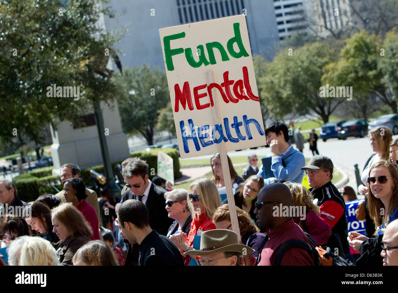 Citizens attend rally and hold up signs asking the Texas legislature for additional funding for mental health services - Stock Image