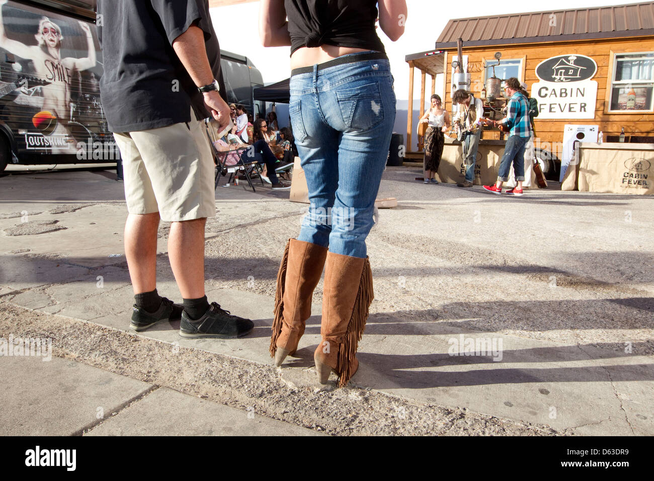 Couple With Female Wearing Jeans And Cowboy Boots Listen To Music At