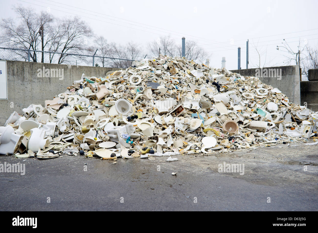 A pile of broken toilets and sinks at a city dump. - Stock Image