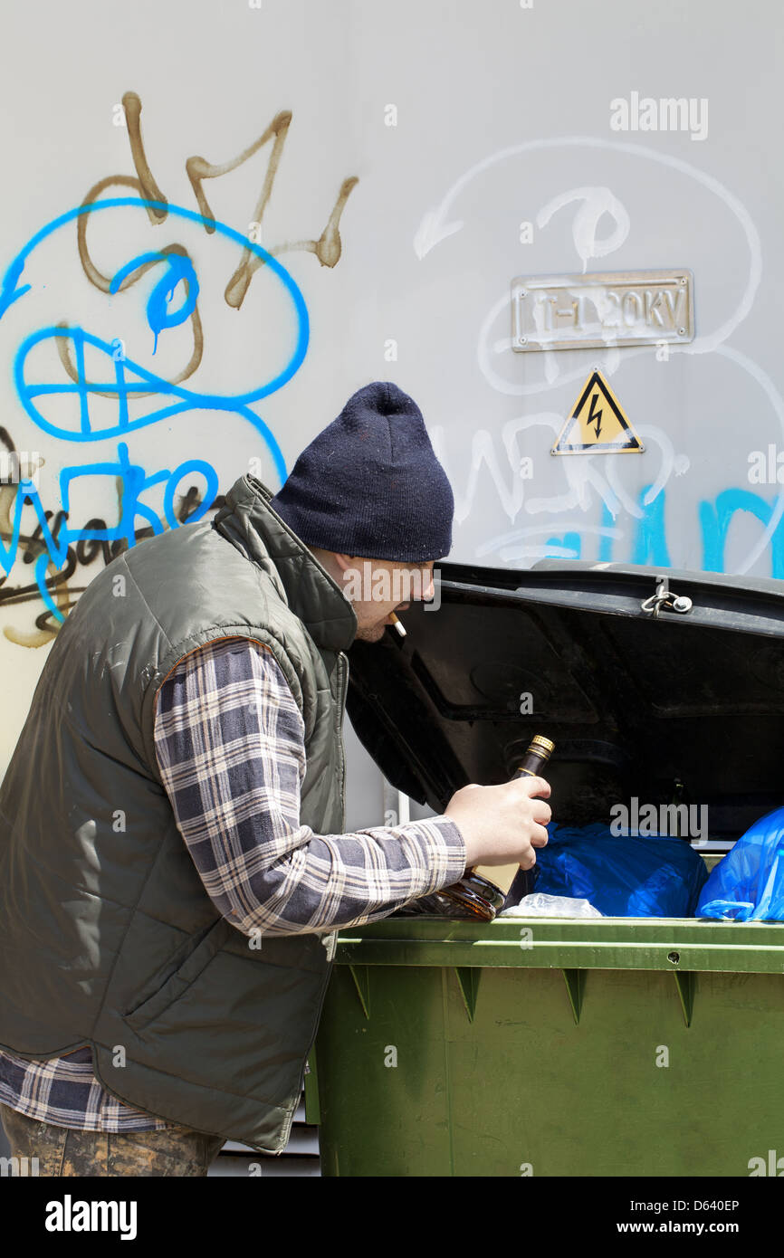 Tramp digging in dumpster - Stock Image