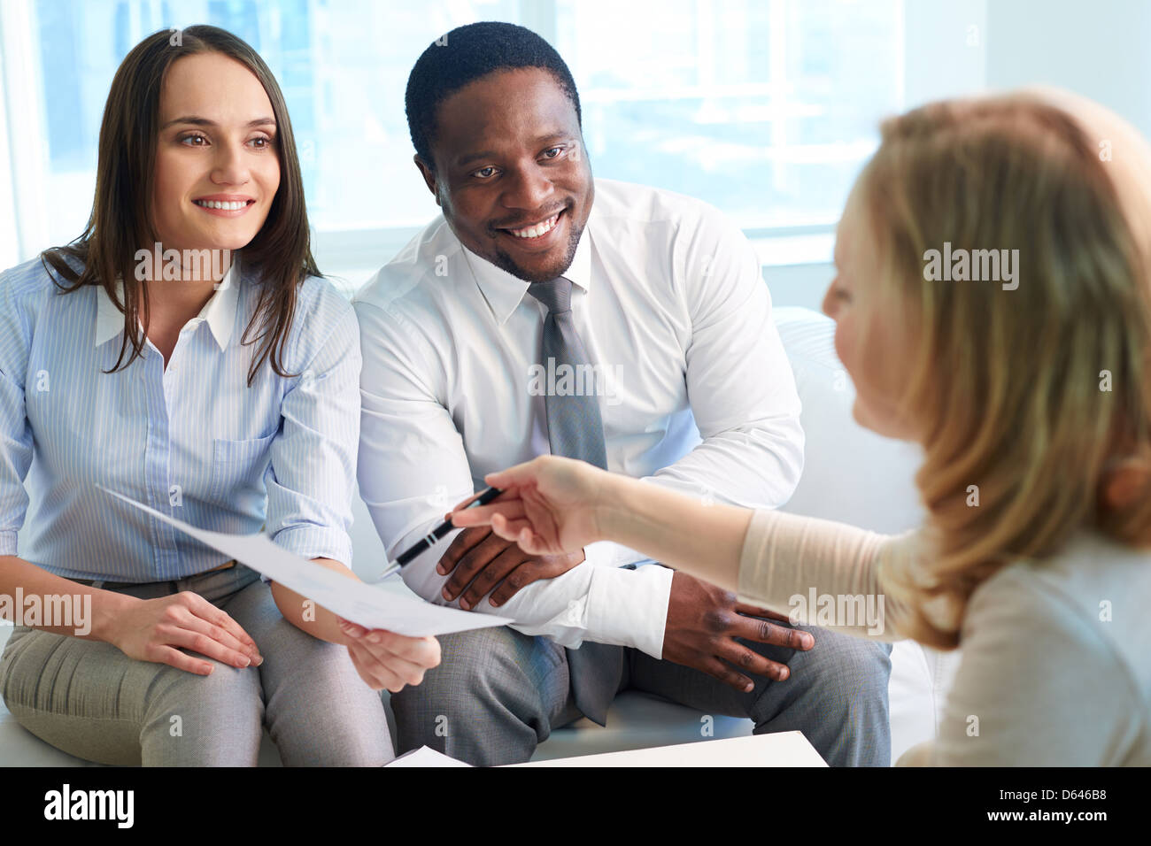 Image of confident colleagues looking at their business partner offering them to sign paper at meeting - Stock Image