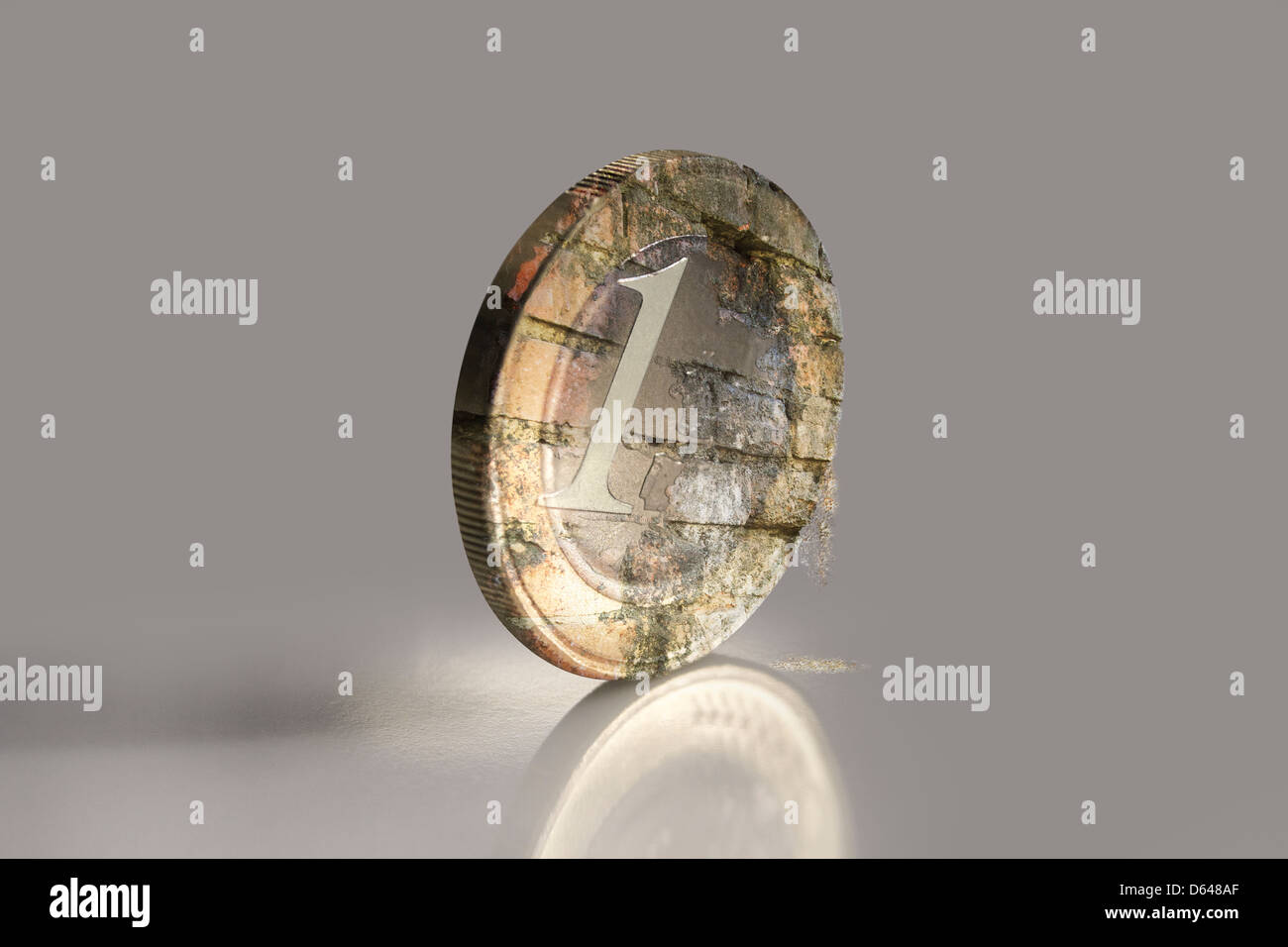 Crumbling Euro coin with its undamaged reflection - Stock Image
