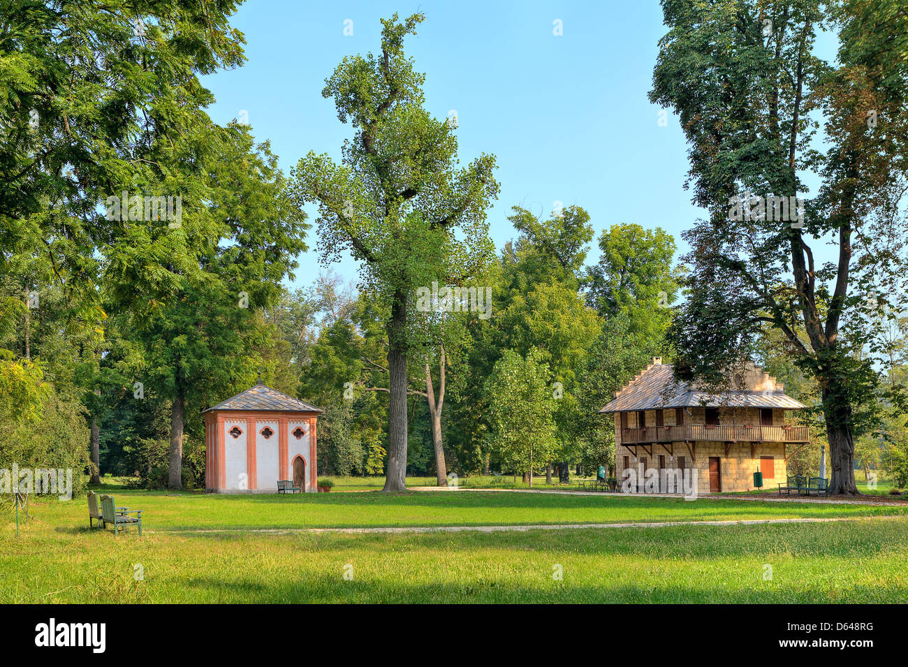 Small guest houses on green lawn among trees at Racconigi - royal park in Piedmont, Northern Italy. - Stock Image