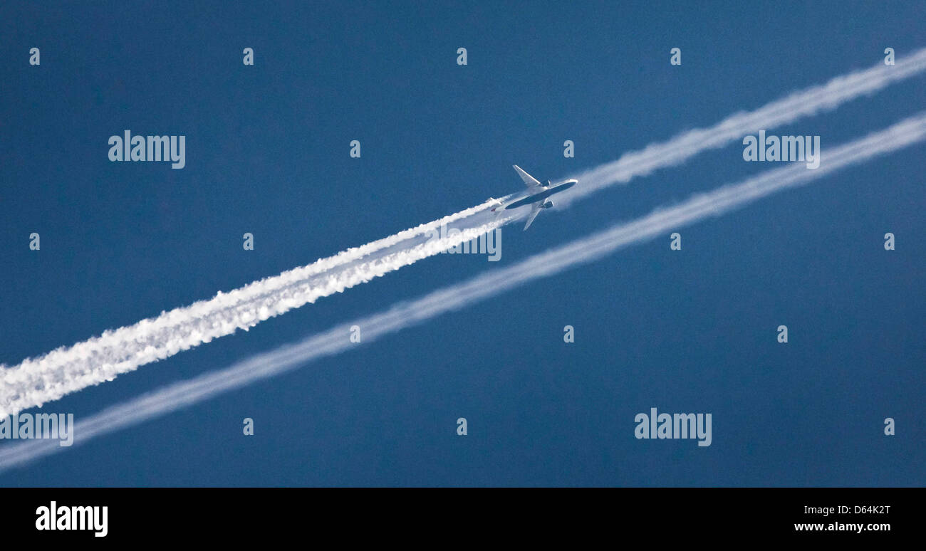 A twin jet aircraft leaves behind contrails in the blue evening sky above Frankfurt Main, Germany, 28 May 2012. - Stock Image