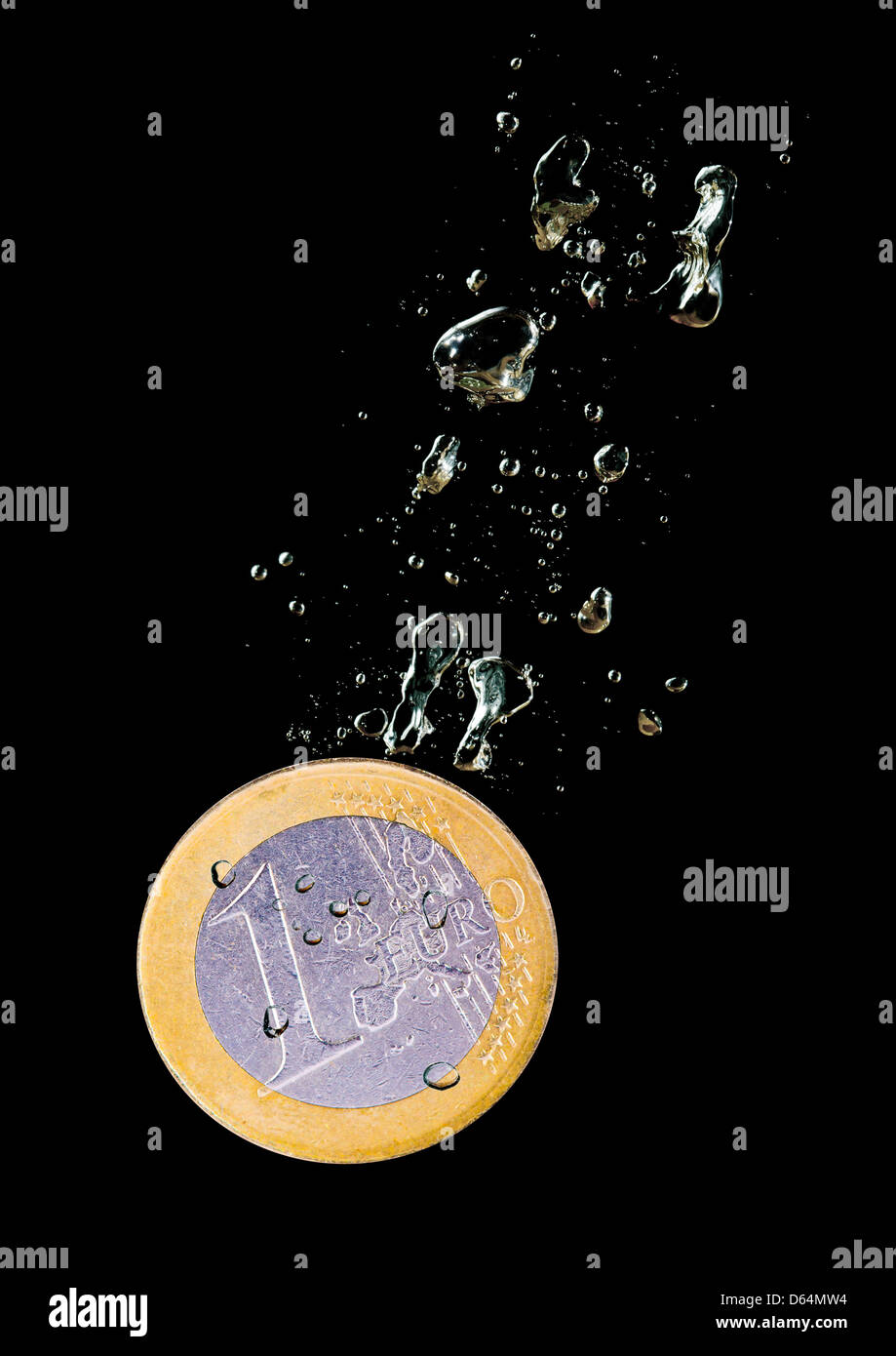 Concept with euro coin sinking in water over black background - Stock Image