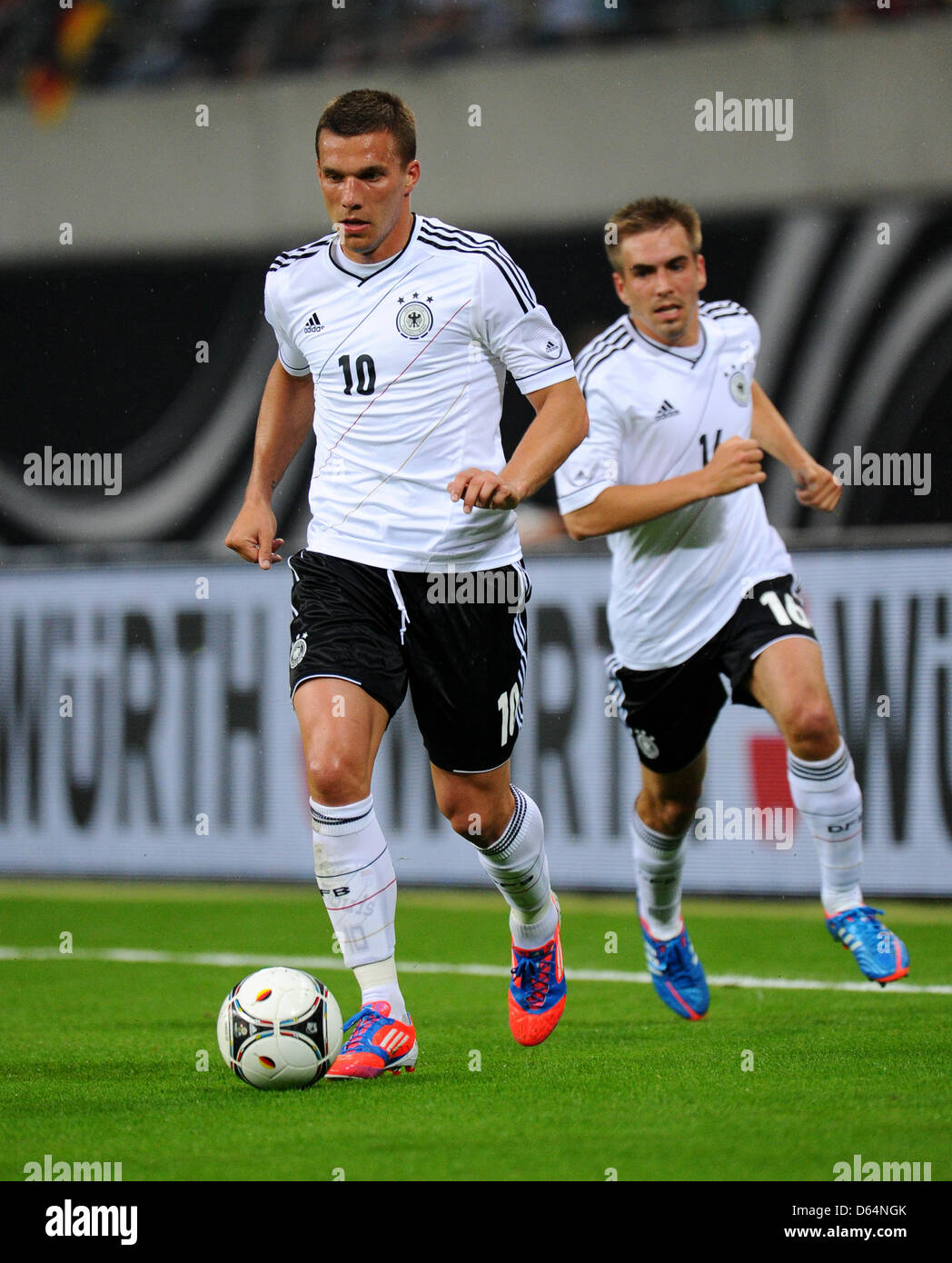 Germanys Lukas Podolski With Philipp Lahm Plays The Ball During
