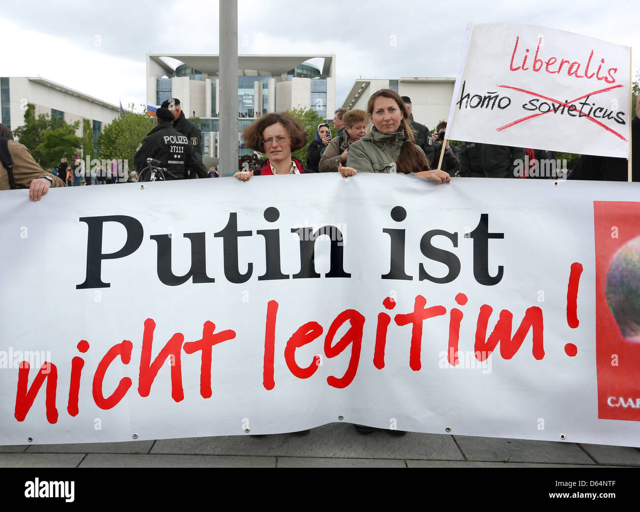 People protest with a sign reading 'Putin is not legitimate' against Russian President Putin in front of - Stock Image