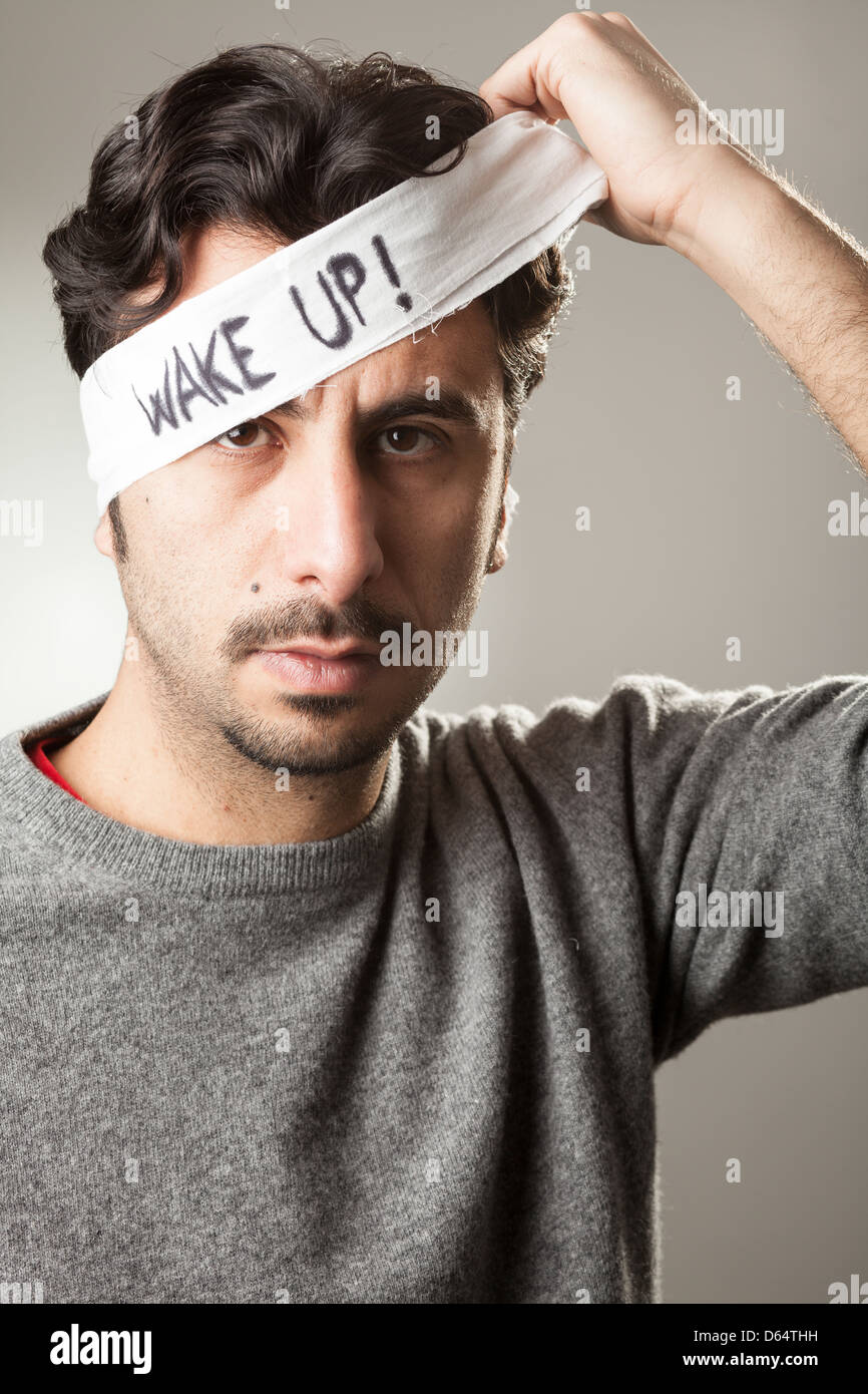 Man Taking Off a Bandage from His Eyes with 'Wake Up!' Written On It - Stock Image