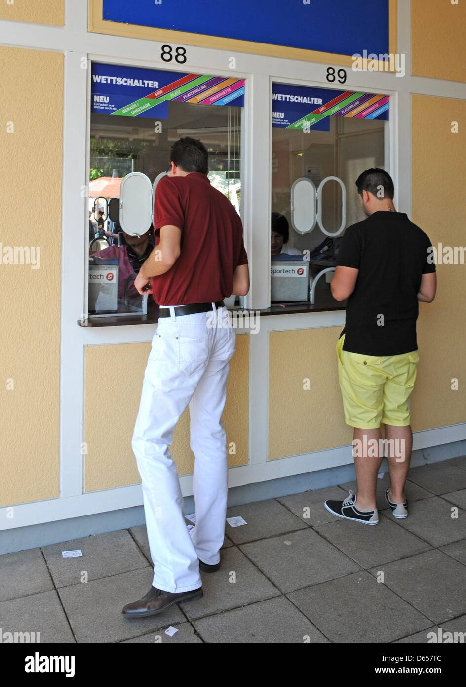 Two Men Hand In Their Betting Slips At The Betting Booth On The Horse Stock Photo Alamy