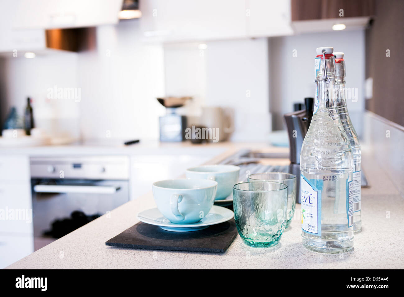 Carefully laid out cups, saucers, glasses and water bottles in a contemporary kitchen - Stock Image