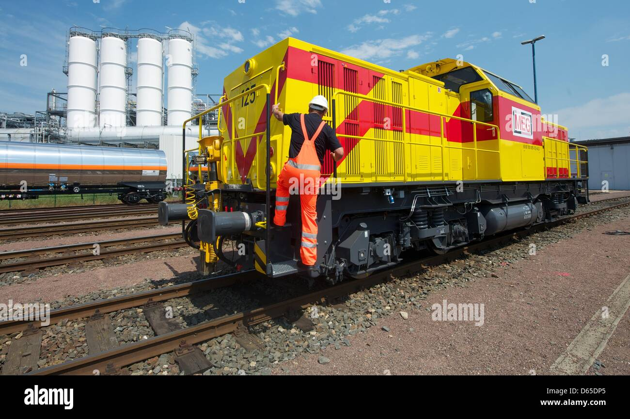 A worker climbs onto a locomotive with a hybrid engine at a compound of Mitteldeutsche Eisenbahngesellschaft mbH - Stock Image