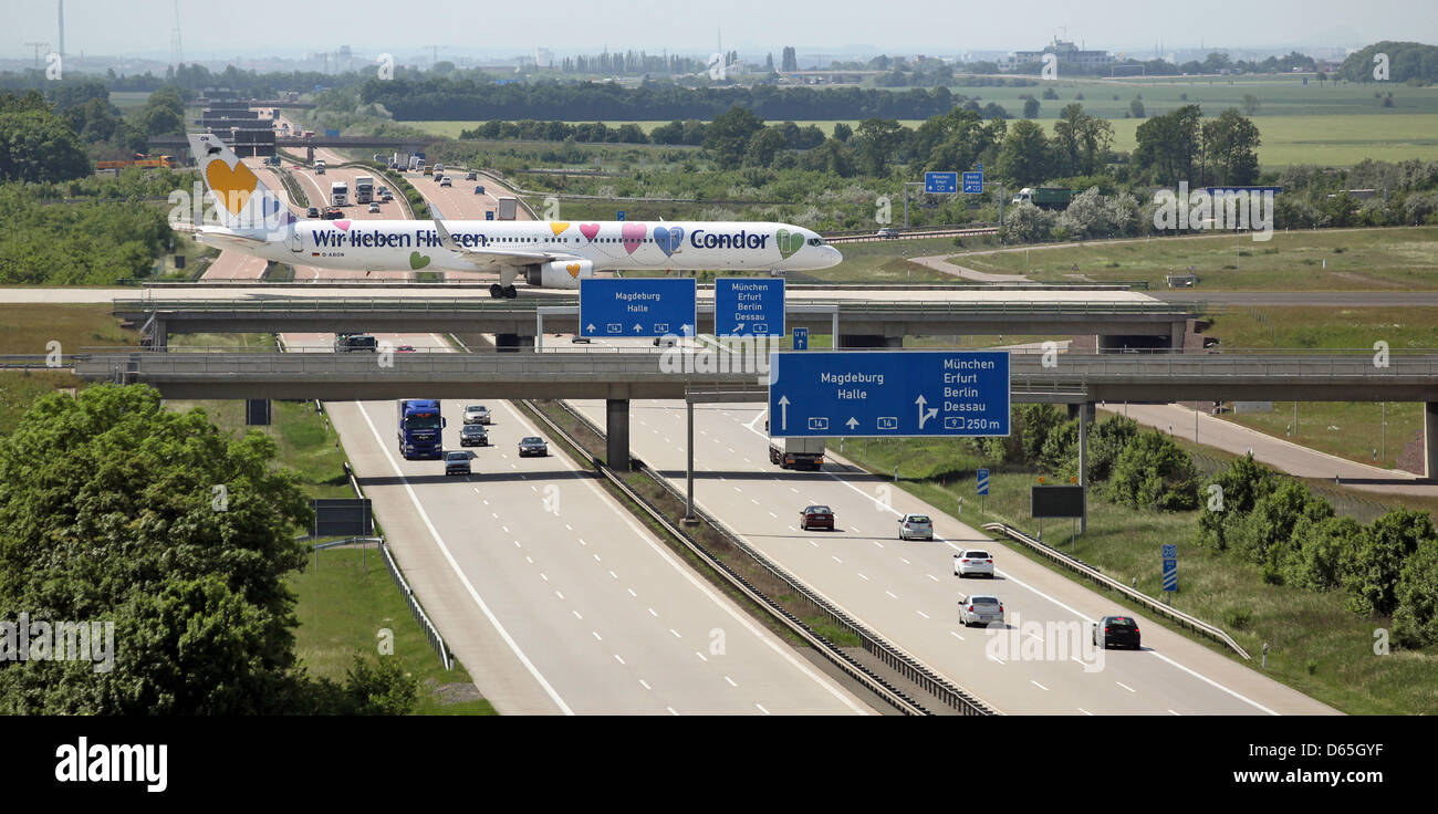 An airplane from Condor airlines is driven across a bridge over Autobahn 14 to take off at Leipzig-Halle Airport Stock Photo