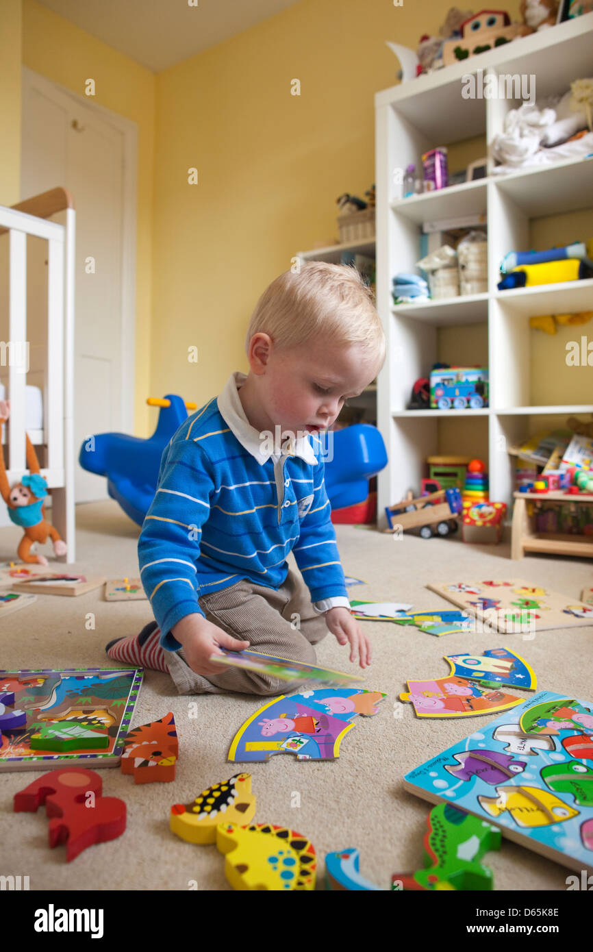 2 year old boy plays with various jigsaw puzzles in his bedroom, England, UK