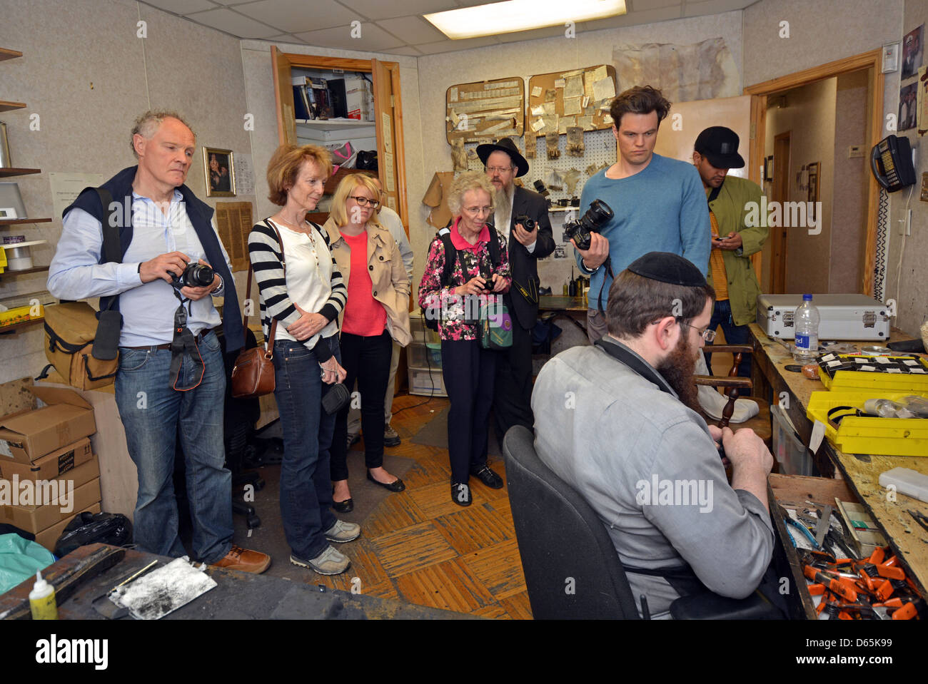 A tour group visits a place where teffilin (phylacteries) are made in Crown Heights, Brooklyn, New York - Stock Image