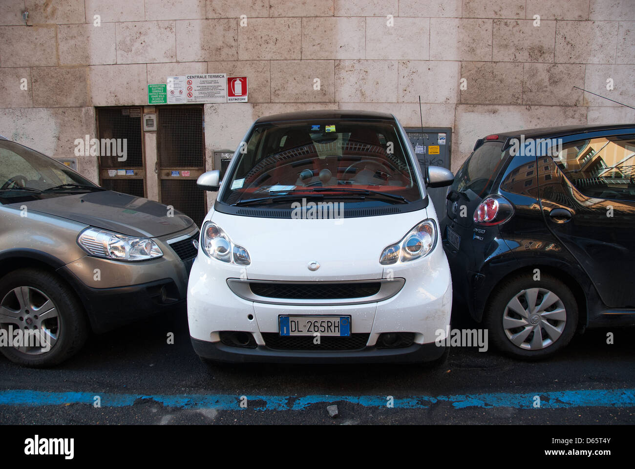 ROME, ITALY. A Smart car parked perpendicular to the road and other parked vehicles (driver unable to get in!). - Stock Image