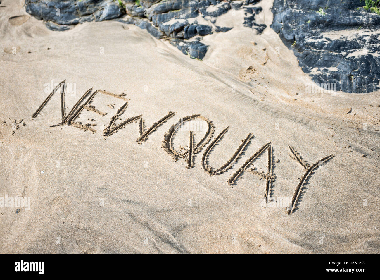 The word Newquay written in sand on a beach - Stock Image
