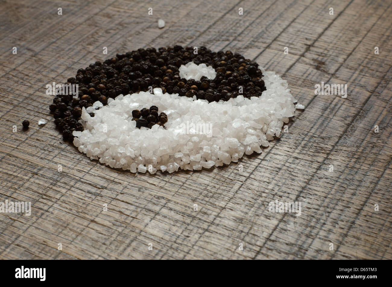 Seasalt and Peppercorns shaped to form a Yin Yang on an Oak Wood Chopping Board - Stock Image