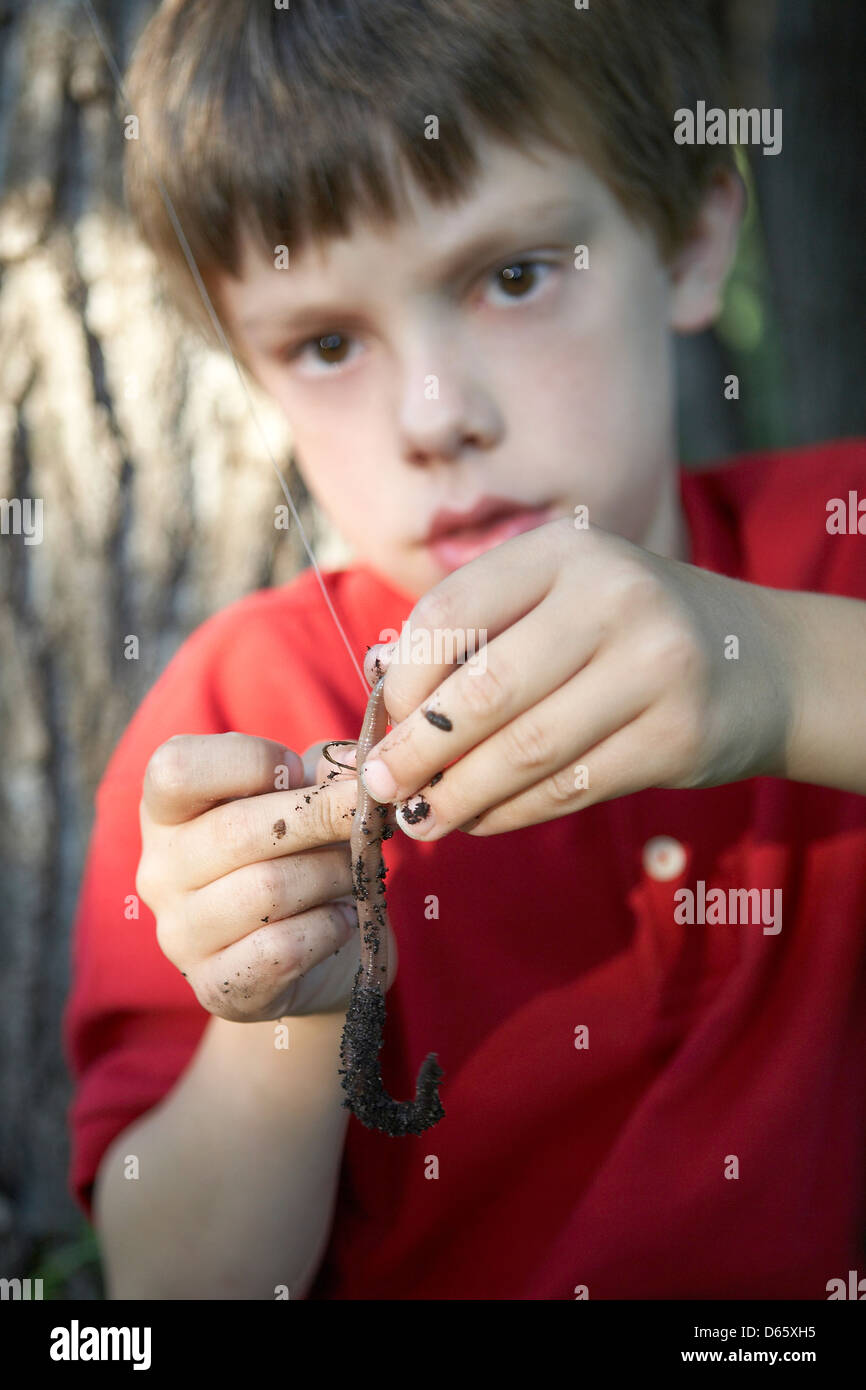 8 year old boy hooking worm Stock Photo