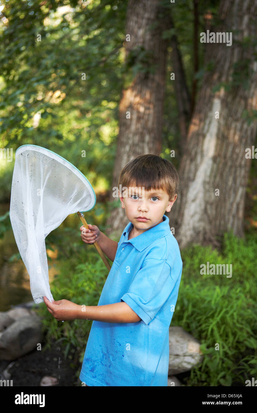 7 year old boy with fishing net - Stock Image