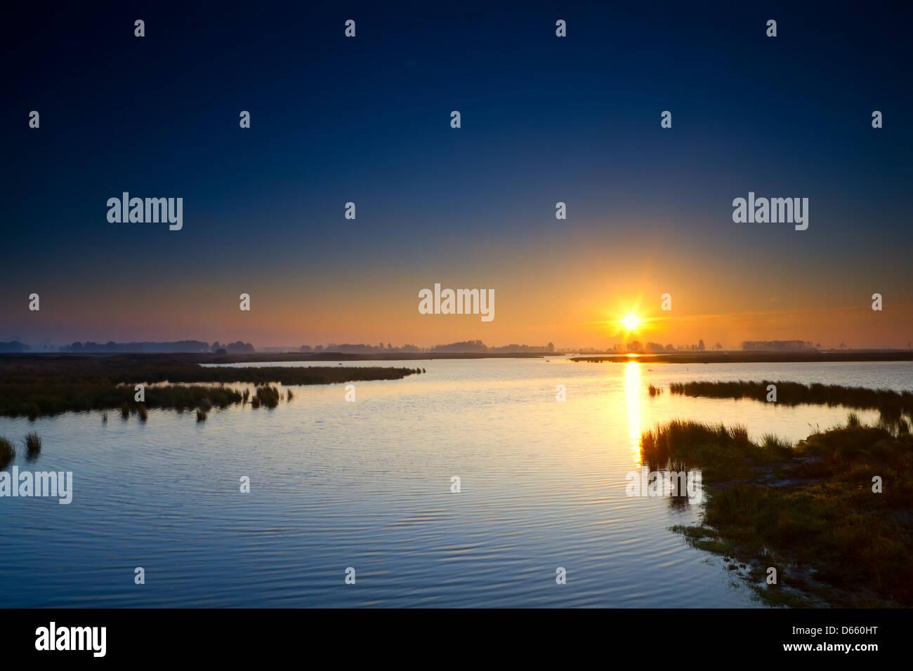 sun rising up over blue lake Stock Photo